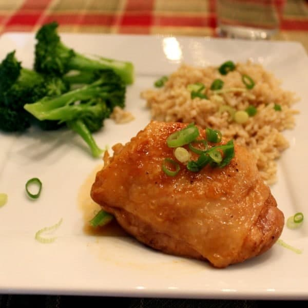 Close up view of a chicken thigh on a plate, sprinkled with green onions. Broccoli and rice are pictured in the background.