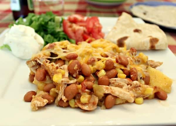 A messy pile of pinto beans, chicken, cheese, and corn on a white plate.