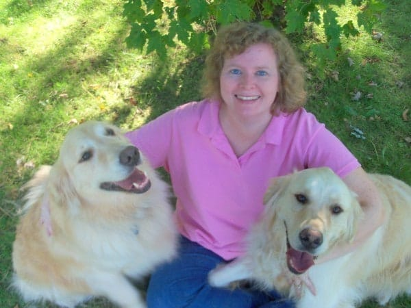 Author Brett Simber wearing a pink shirt and blue skirt, with two golden retrievers.