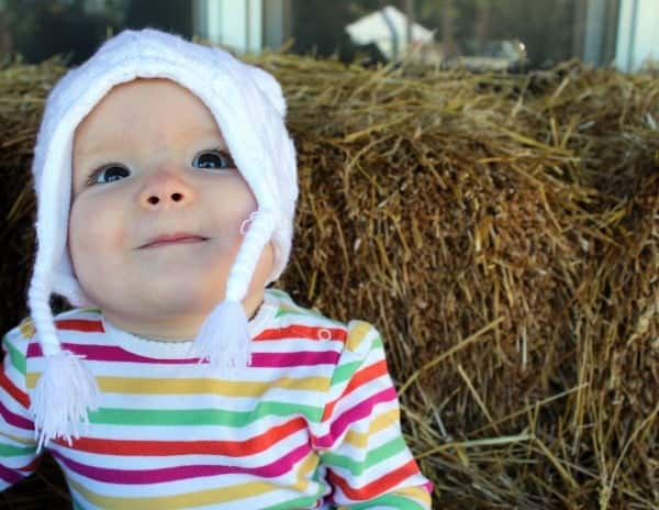 Very young child in a white hat against a background of hay.