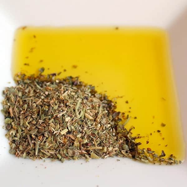 Overhead view of shallow dish containing Italian spice and olive oil.