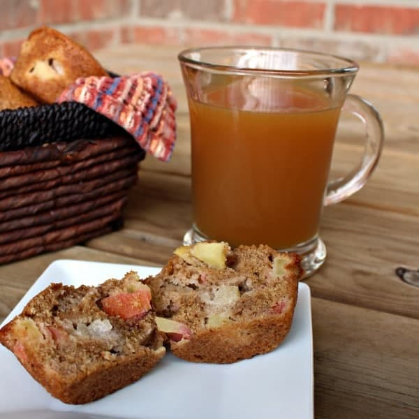 Apple muffin split in two halves on a white plate. A clear glass mug of hot apple cider is also pictured.