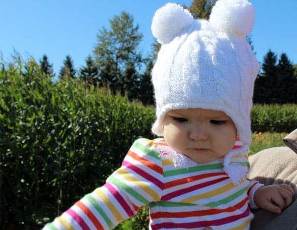 Cute baby girl in a striped shirt and a white hat.