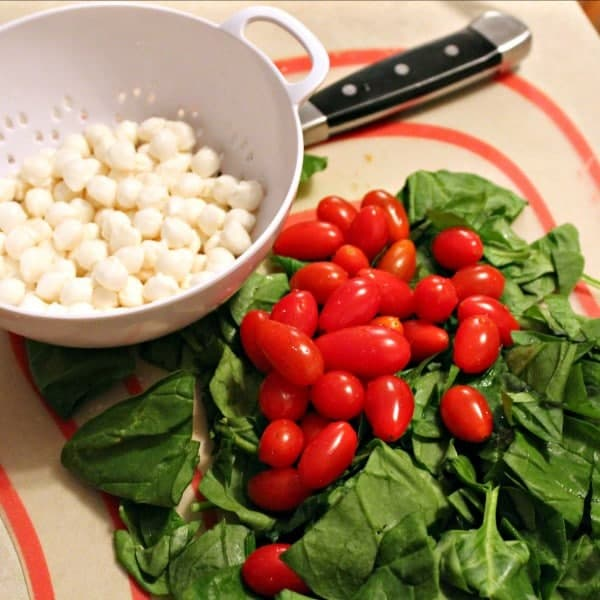 Overhead shot of a pile of fresh spinach leaves, with several grape tomatoes piled on top. Along side is a small white colander containing many mozzarella pearls.