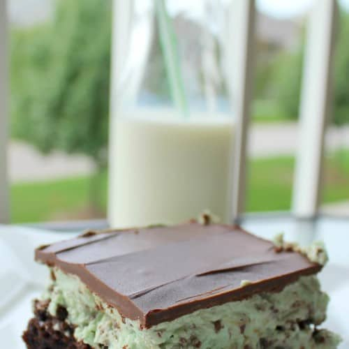 Close up view of a layered brownie - on the bottom, brownie, next green mint chocolate icing, and topped with melted chocolate.