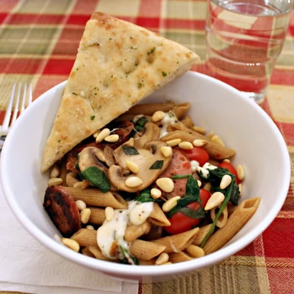 White bowl with pasta, a wedge of bread balanced on edge, on plaid tablecloth with water glass, fork, and napkin in background