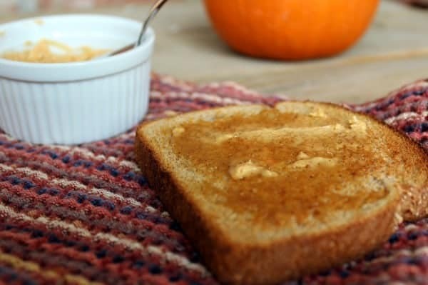 Close up view of a slice of toast with melting butter. In the background are a small white bowl and a pumpkin.