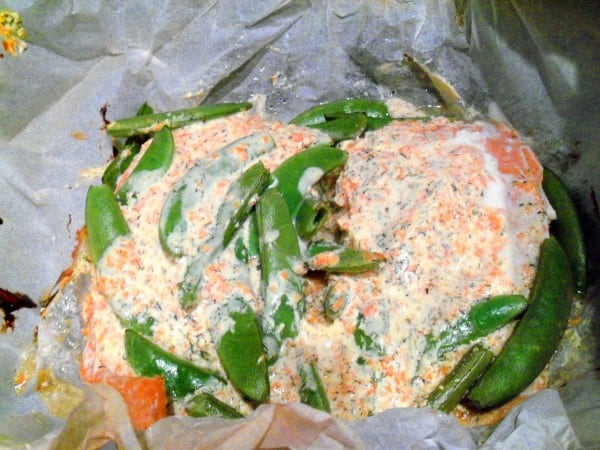 Salmon coated in sour cream with peas and carrots.