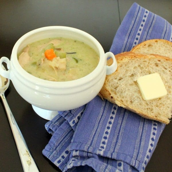 Creamy soup in a bowl with bits of chicken, carrots and celery showing. Also pictured are a blue linen, bread with butter, and a spoon.