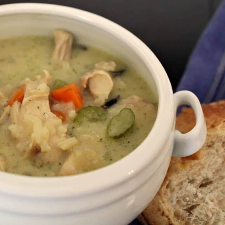 White crock-style bowl with creamy soup in it. Bits of chicken, rice, celery, and carrots are visible.