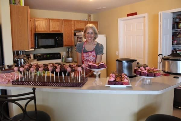 Mom in kitchen, wearing apron, surrounded by cupcakes and cake pops.