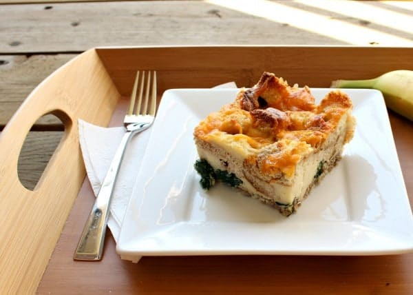 White plate containing a square piece of breakfast casserole on a wooden tray, along with a fork, white napkin and banana.