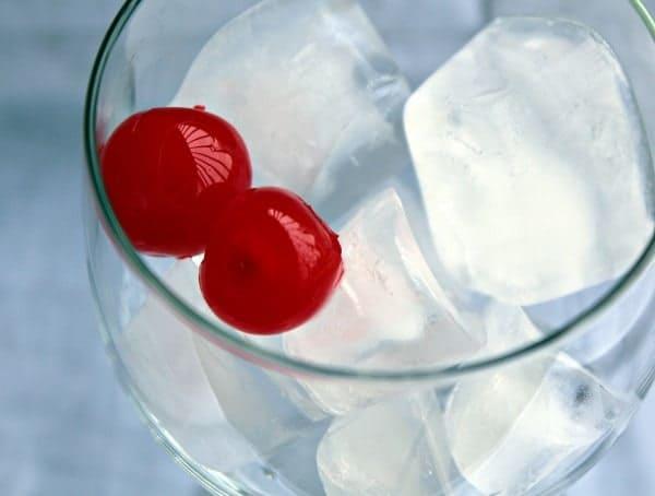 Close up of wine glass containing ice and 2 maraschino cherries.