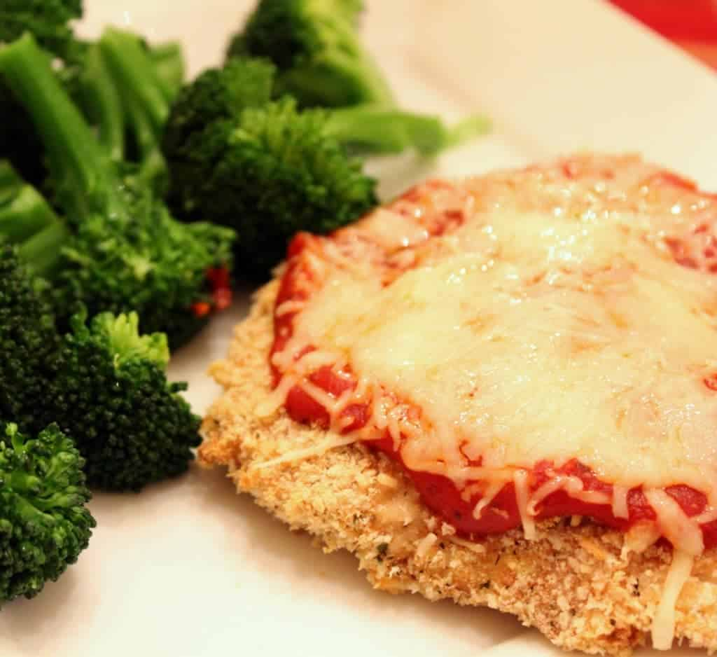 Partial closeup of baked chicken Parmesan with steamed broccoli on white plate.