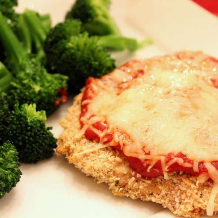 Partial image of chicken parmesan accompanied by steamed broccoli on white plate.