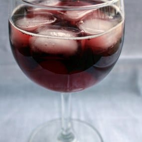 Stemmed wine glass containing cherry spritzer with ice cubes.