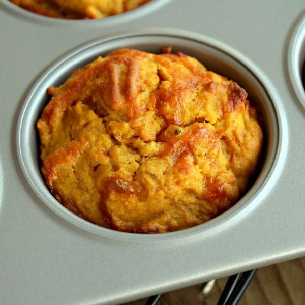 Close up view of a pumpkin muffin in a tin. Cheddar and black pepper are visible in the muffin.