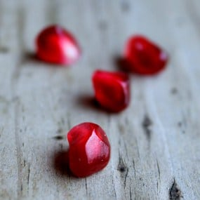 Pomegranate seeds on wooden background.