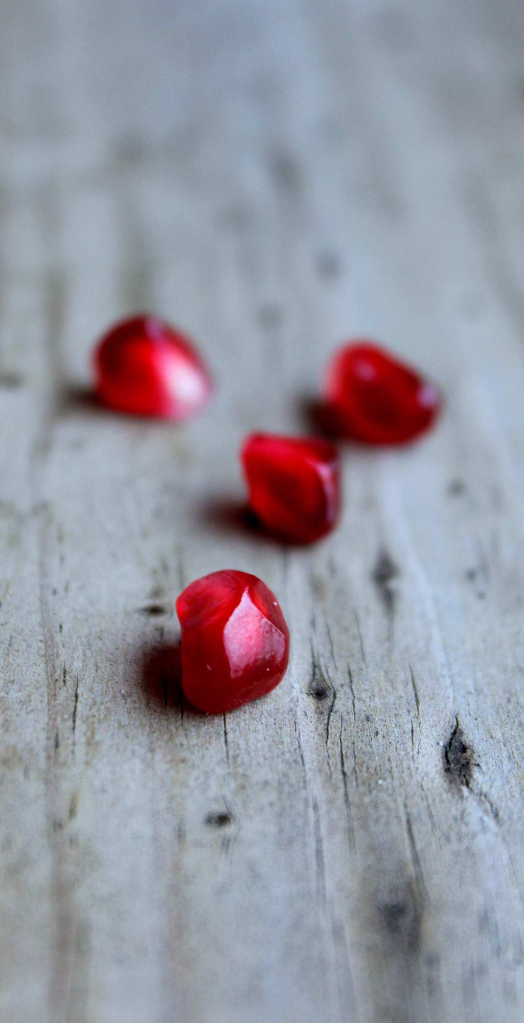 Pomegranate arils on a wooden surface.