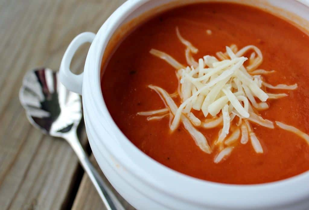 Tomato soup in a white bowl, sprinkled with cheese.
