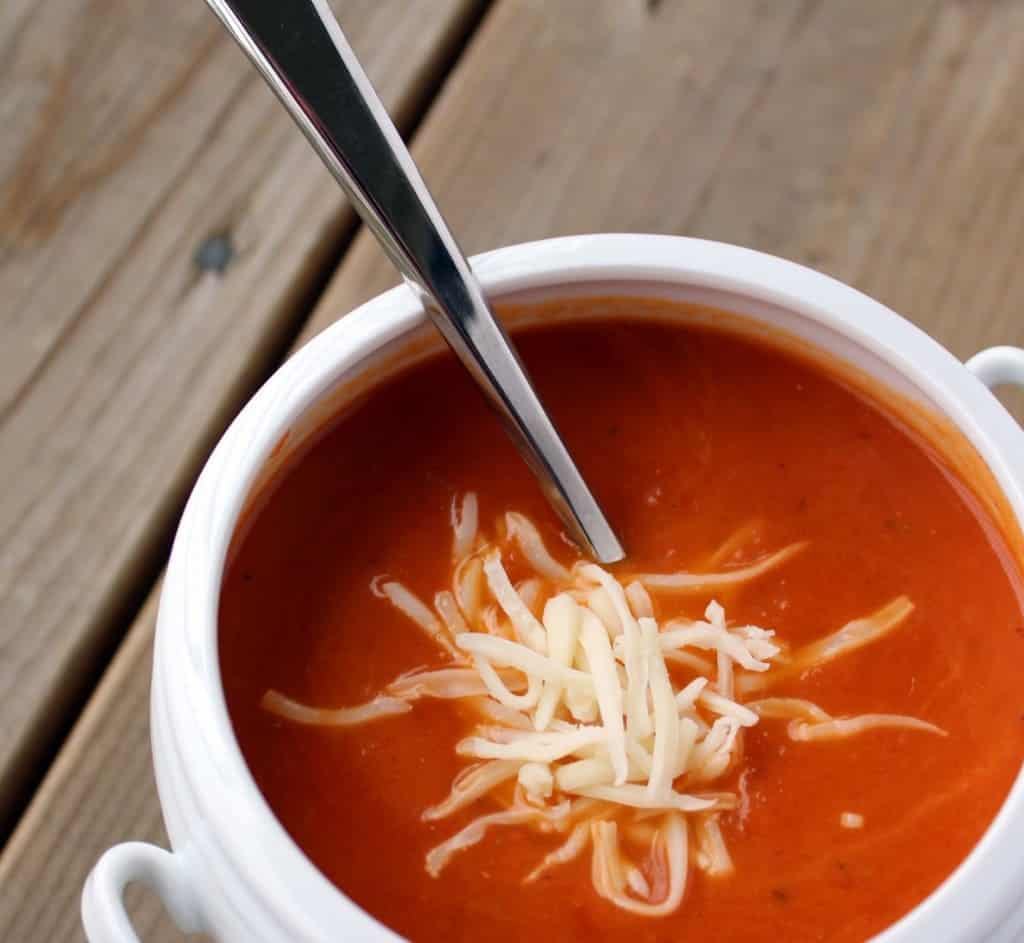 Tomato soup in a white bowl, sprinkled with cheese. Spoon is in a bowl.