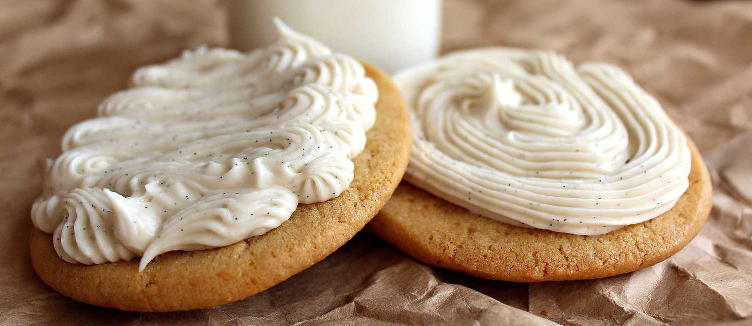 Two cookies with piped-on frosting in front of a glass of milk.