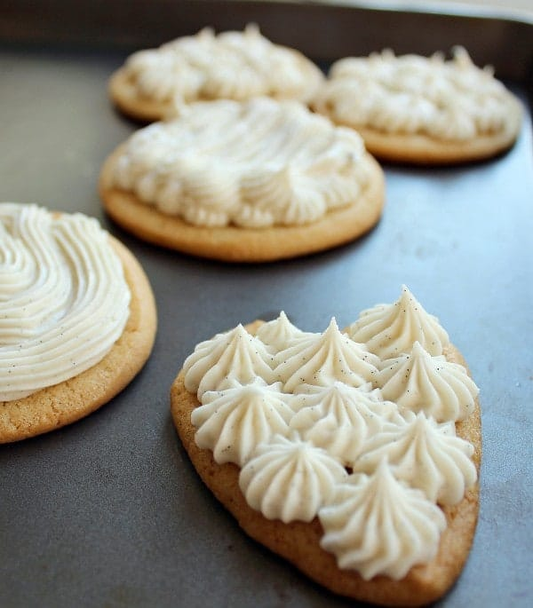 Cookies on a pan, topped with piped-on vanilla bean frosting.