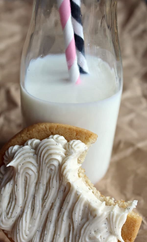Frosted cookie with a bite taken out of it, leaning against a bottle of milk with two straws in it.