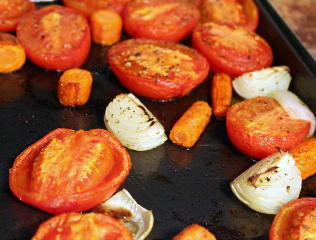 Roasted tomatoes, onions, and carrots on a sheet pan.