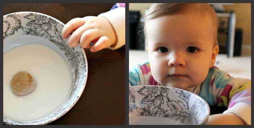 Cute baby next to a bowl of granulated sugar with a rolled cookie dough ball in it.