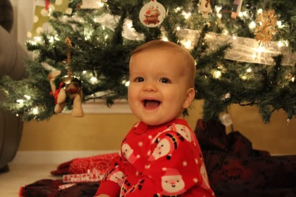 Young girl in front of a Christmas tree.