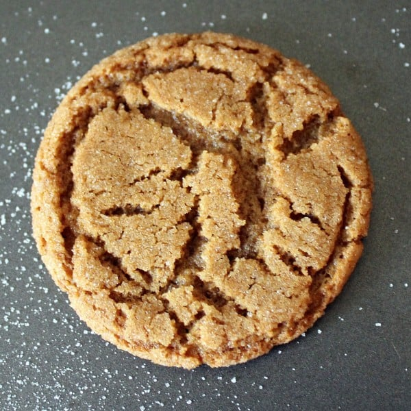 Overhead view of one light brown cookie made with ginger, crackled on top. Granulated sugar is also pictured.