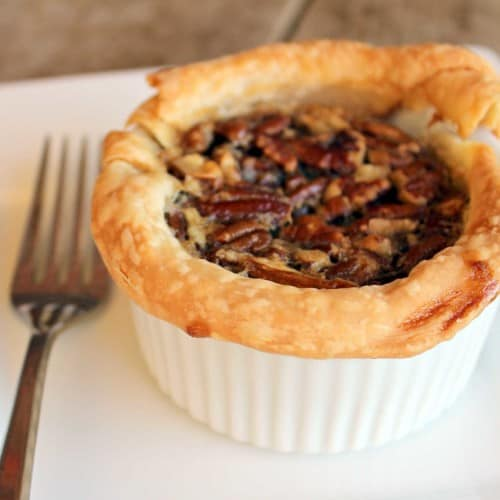 One pecan pie, in ramekin on square white plate with fork.