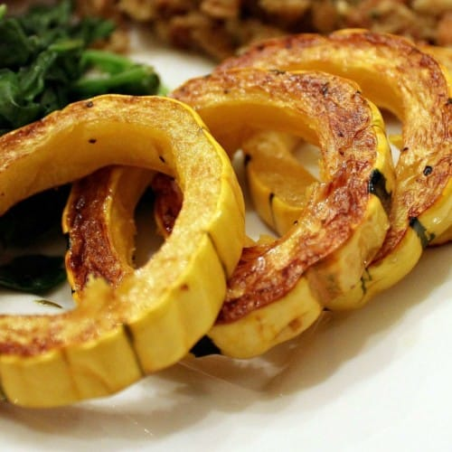 Four rings of roasted delicata squash on a white plate, with other food visible in background.