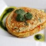 Quinoa pancake with vinaigrette on square white plate.