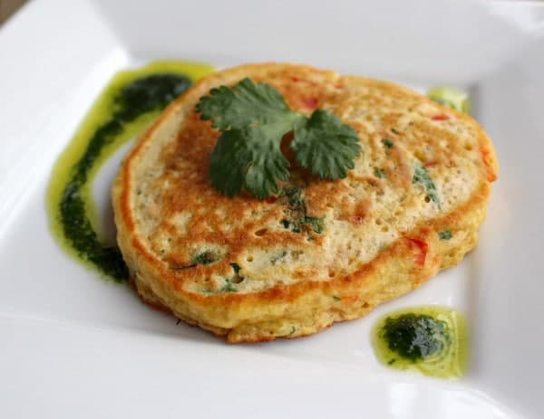 A single pancake on square white plate with vinaigrette, garnished with sprig of parsley.