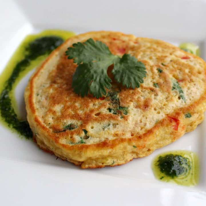 Quinoa pancake with vinaigrette on square white plate.