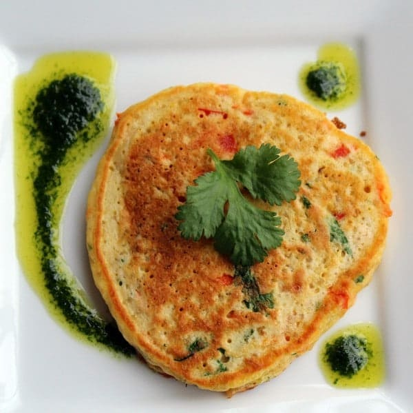 Overhead of pancake with vinaigrette on square white plate.
