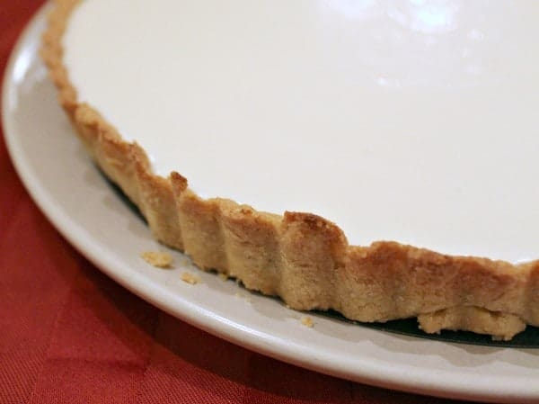 Partial closeup of whole tart on plate, showing crust and yogurt filling.