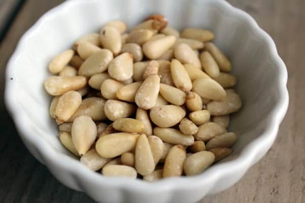 Small white dish containing pine nuts.
