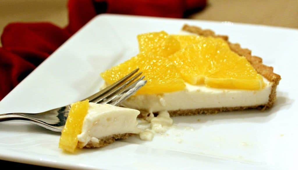 A slice of the tart, with a fork inserted, on white square plate.