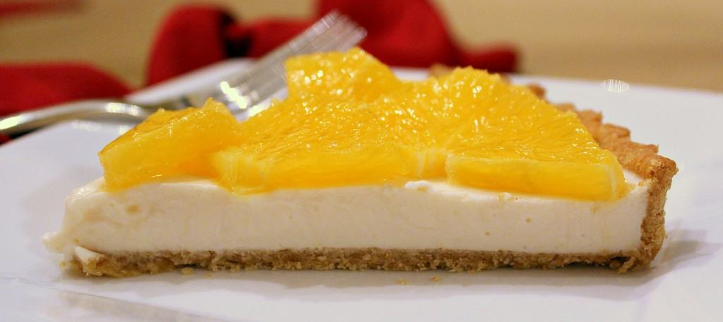 Slice of yogurt tart, topped with oranges, on white plate with fork.