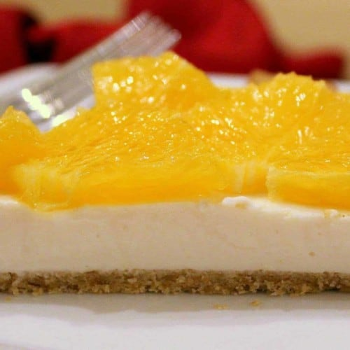 Slice of yogurt tart on white plate with fork.