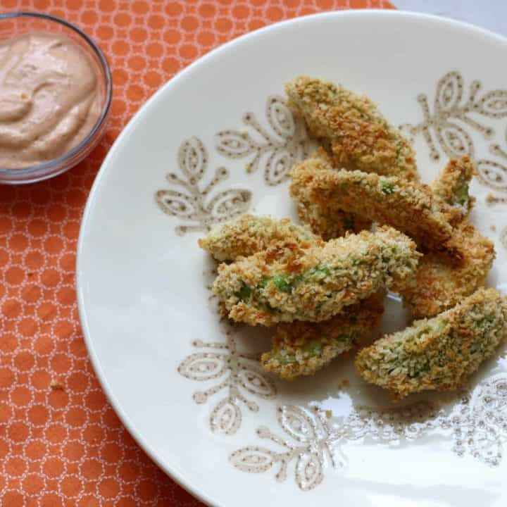 Avocado fries on white plate with small bowl of chipotle mayo.