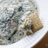 Partial view of spinach dip in bowl with cracker.