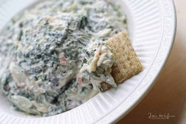 Close up of spinach dip in white bowl with Triscuit cracker inserted.
