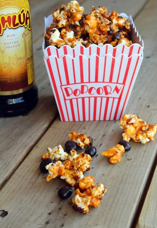 Caramel cor in popcorn container with Kahlua bottle in background.