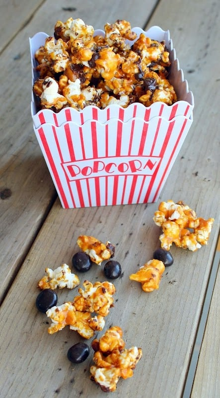 Caramel corn in red striped popcorn container with some scattered around it.