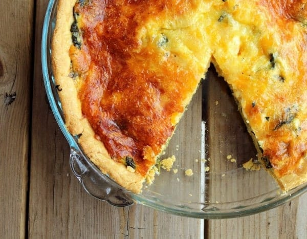 Overhead image of a spinach quiche in a glass pan with one slice removed. It is placed on a wooden background.