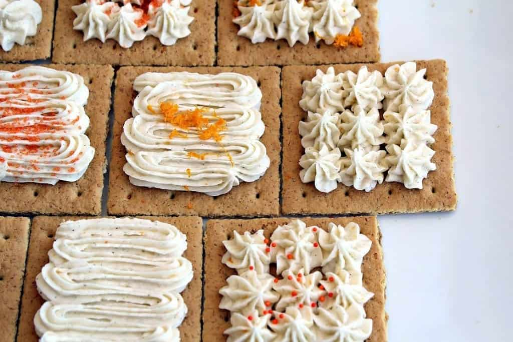 Top view of graham crackers topped with frosting in decorative patterns.